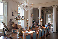 A collection of stuffed birds strut their stuff down the dining table, surrounded by an array of other fantastical beasts