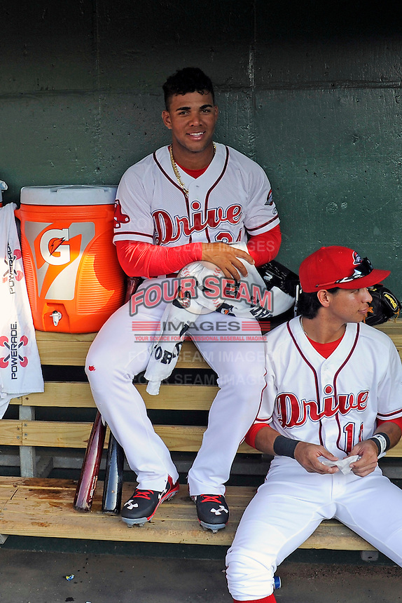 Second baseman Yoan Moncada of the Greenville Drive, top, sits in the dugout with Marricio Dubon (10) before a game against the Lexington Legends on Tuesday, May 19, 2015, at Fluor Field at the West End in Greenville, South Carolina. The Cuban-born 19-year-old Red Sox signee has been ranked the No. 1 international prospect in baseball by Baseball America. (Tom Priddy/Four Seam Images)