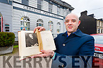 Barty Flynn holding Carnegie's 99 year old biography outside the Old Carnegie Library