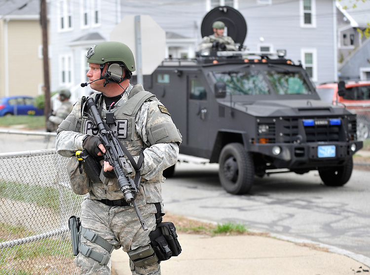 Police in tactical gear conduct a search for a suspect in the Boston Marathon bombings in Watertown, Mass. on Friday, April 19, 2013. Photo by Christopher Evans