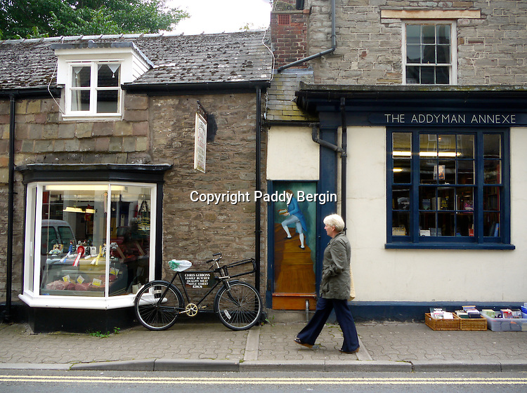 A woman walks past a bookshop in Hay-on Wye. A painted doorway gives the impression of an entrance and a figure climbing the stairs. Hay-on-Wye is well known for its Book Festivals.<br />
