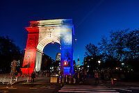 New York, NY - 15 November 2015 NYC  The arch in Washington Square Park and the World Trade Center light up in solidarity with Paris.  Beneath the arch is a candlelight shrineto commemorate the victims of the 13 November Paris terror attacks.