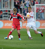 Chicago midfielder Chris Rolfe (17) passes the ball while being pressured by New York defender Markus Holgersson (5).  The Chicago Fire defeated the New York Red Bulls 3-1 at Toyota Park in Bridgeview, IL on April 7, 2013.