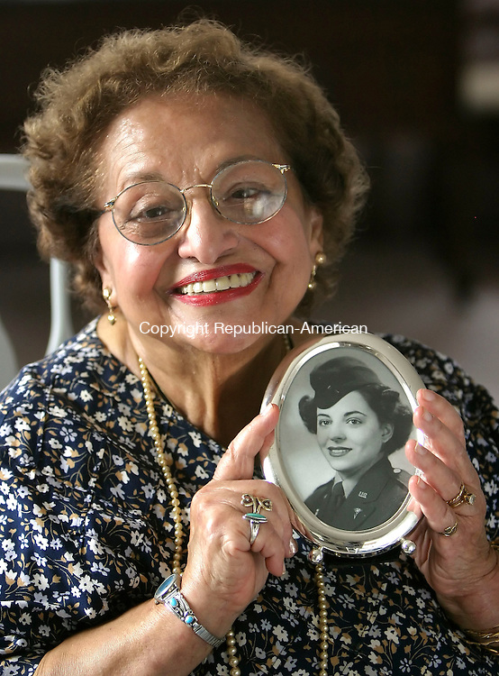 WATERBURY, CT, 03/27/07- 032707BZ01- Alda Shaker Hannon poses with a photograph when she was a 20-year-old Lieutenant in the U.S. Army during WWII. Shaker Hannon recently self-published a book about her experiences titled &quot;Adventures of a WWII Army Nurse.&quot;<br /> Jamison C. Bazinet Republican-American