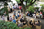© Joel Goodman - 07973 332324 . 27 July 2013 . Hulme Community Garden Centre , Old Birley Street , Hulme , Manchester M15 , UK . Visitors sit on haystacks around a music stage in front of the greenhouse as an acapella singing group perform . Hulme is Where the Art Is festival . Photo credit : Joel Goodman
