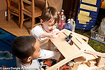 Education Preschool Headstart 4 year olds two boys playing together with human figures and doll house