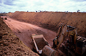 Trombetas bauxite mine, Para, Brazil. Large mechanical digger loading ore onto a dumper truck.