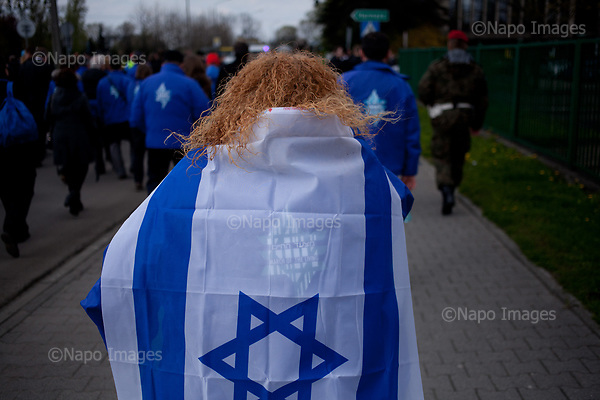 OSWIECIM, POLAND, APRIL 24, 2017:<br /> Woman with ginger hair is walking wrapped in Israeli flag in the &quot;March of The Living&quot; an annual march between two camps of the Auschwitz concentration camp<br /> (Photo by Piotr Malecki / Napo Images)<br /> ###<br /> OSWIECIM, 24/04/2017:<br /> Marsz Zywych w Oswiecimiu.<br /> Fot: Piotr Malecki<br /> <br /> ###ZDJECIE MOZE BYC UZYTE W KONTEKSCIE NIEOBRAZAJACYM OSOB PRZEDSTAWIONYCH NA FOTOGRAFII###