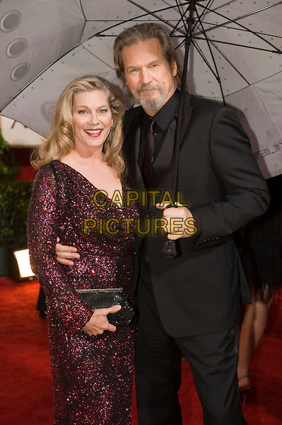 SUSAN STOCK & JEFF BRIDGES.Arrivals at the 67th Golden Globe Awards held Beverly Hilton, Beverly Hills, California, USA..January 17th, 2010.globes half length beard facial hair umbrella raining married husband wife red beaded sparkly dress clutch bag suit black goatee.CAP/AW/HFPA.Supplied by Anita Weber/Capital Pictures