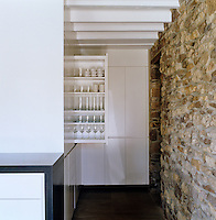 A run of white lacquered units conceals deep pull-out full-height shelves and adds to the simplicity of this kitchen