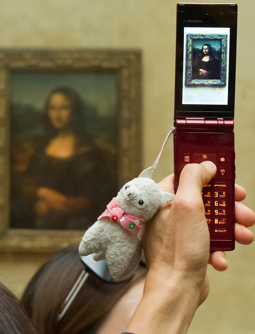 The mobile phone of a visitor to the Louvre Museum in front of the Mona Lisa (La Joconde), painted by Leonardo de Vinci between 1503 and 1506. The Louvre Museum is housed in the former Louvre Palace, on the right bank of the Seine, adjoining the Tuileries Gardens in Paris. Monday 21st November 2011.