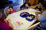 Sophia, left, and Dennis Sawyer, right, help their children, from left, Frances, Isaiah, and Daniel, with their homework January 27, 2010 in Sacramento, Calif. The Sawyer family receives $540/month in CalWORKs assistance from the state of California. Dennis is currently unable to work while recovering from cancer, and Sophia hasn't been able to find work. Gov. Arnold Schwarzenegger has proposed eliminating the CalWORKs program in an effort to balance the state's budget. CREDIT: Max Whittaker for The Wall Street Journal.CABUDGET