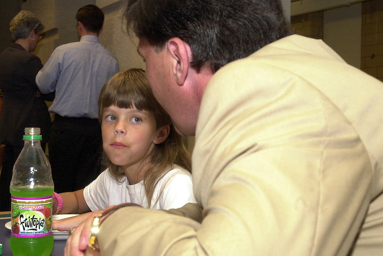 1pizza062001 -- Congressman Robert Ehrlich Jr., R-MD, sits with Daniela Hendricks age seven of Sandy Springs Elementary for a pizza reward for meeting the Congressman's reading challenge.