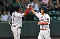 Second baseman Nick Lovullo (36) of Greenville Drive, right, is congratulated by Tyler Hill (7) after scoring a run in a game against the Greensboro Grasshoppers on Tuesday, April 25, 2017, at Fluor Field at the West End in Greenville, South Carolina. Greenville won, 5-1. (Tom Priddy/Four Seam Images)