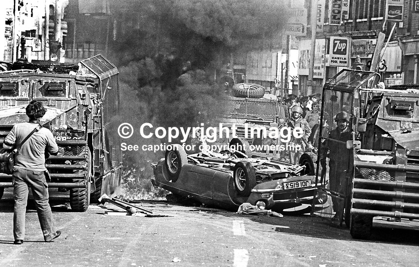The Silver Jubilee visit of Queen Elizabeth II to N Ireland on 10th &amp; 11th August 1977 sparked serious rioting in Belfast as those opposed to the visit tried to reach the city centre. Soldiers at the scene of a burning overturned car blocking a main route.  197708100074d<br /> <br /> Copyright Image from Victor Patterson, 54 Dorchester Park, Belfast, UK, BT9 6RJ<br /> <br /> Tel: +44 28 9066 1296<br /> Mob: +44 7802 353836<br /> Voicemail +44 20 8816 7153<br /> Email: victorpatterson@me.com<br /> Email: victorpatterson@gmail.com<br /> <br /> IMPORTANT: My Terms and Conditions of Business are at www.victorpatterson.com