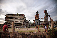 People watching a football (soccer) game being played in the grounds of the former Grand Hotel building. Once a luxury destination for the wealthy and the continent's biggest hotel, the building is now a concrete shell and home to about 6,000 squatters. Those unable to occupy one of the rooms sleep in the corridors, basements and even on the roof of the building.
