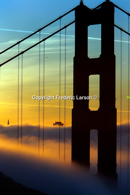 The fog blankets the bay leaving only the Golden Gate Bridge and the tallest of buildings visible at sunrise in San Francisco, California.