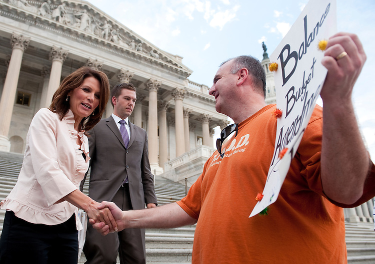 UNITED STATES - AUGUST 1: Presidential candidate Rep. Michele Bachmann, R-Minn., greets Mark Matthews and his family of Kansas City, Mo., as they hold a family protest calling for a balanced budget at the House steps during the vote on the debt ceiling bill in the House of Representatives on Monday, Aug. 1, 2011. (Photo By Bill Clark/Roll Call)