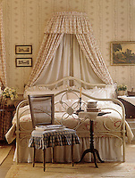 A traditional bedroom with a floral pattern wallpaper. A co-ordinating fabric corona with frill is draped behind a white iron bedstead.