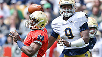 Quarterback Brandon Wimbush (7) is touched for a sack by defensive lineman Daelin Hayes (9) in the third quarter.