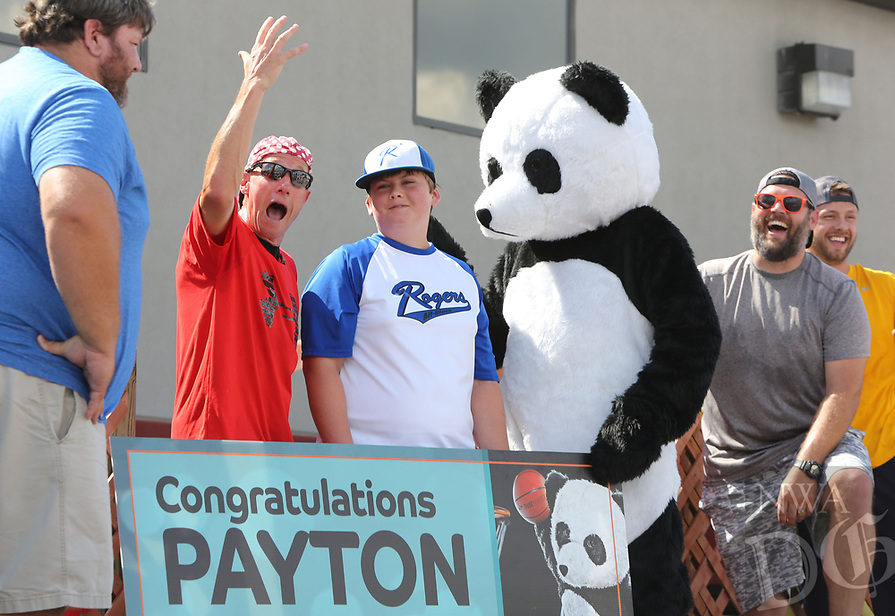 NWA Democrat-Gazette/DAVID GOTTSCHALK   Jason Upton (from left), Payton Upton's father, watches as Jim Sliker, chief executive officer of Central States Manufacturing, Inc., celebrates with Payton, 13, a panda bear, Aric (cq) Bergthold, sales, and Mark Scabarozi, general manager of operations, Wednesday, July 12, 2017, after the announcement of Payton being granted his wish of meeting his favorite YouTube celebrity. The granted wish was made possible by Central States Manufacturing and the Make-A-Wish Mid-South chapter. Employees, family members and Make-A-Wish representatives celebrated with events that included a water balloon toss, paintball and cool treats.