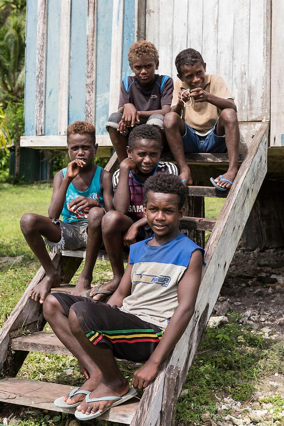 Peava Village, Gatokae Island, Solomon Islands; five boys sitting on the steps leading to their school house