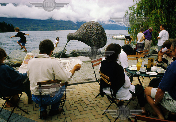 Customers relaxing and children playing at a cafe on the edge of Lake Wakatipu near a large sculpture of a kiwi.