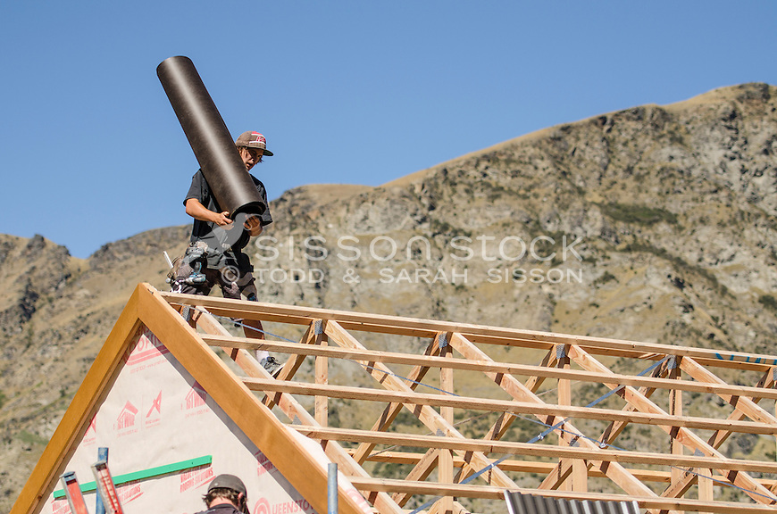 Roofer applying building paper to timber house frame in Queenstown, New Zealand - stock photo, canvas, fine art print