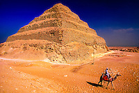 Man on camel passing in front of the Step Pyramid of Saqqara, outside Cairo, Egypt