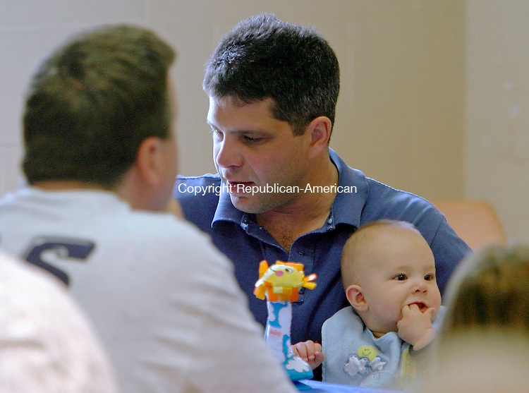 WOODBURY, CT - 19 JUNE 2005 -061905JS04--Ron Wolff of Woodbury holds his 6-month-old son Max in his lap Sunday while enjoying his Father's Day breakfast at the Hotchkissville Fire Company's pancake breakfast in Woodbury. The breakfast is the final in a series of three benefit breakfast's held to raise funds for the company's general equipment fund.  --Jim Shannon Photo--Ron Wolff, Max Wolff, Woodbury, Hotchkissville FIre Company are CQ