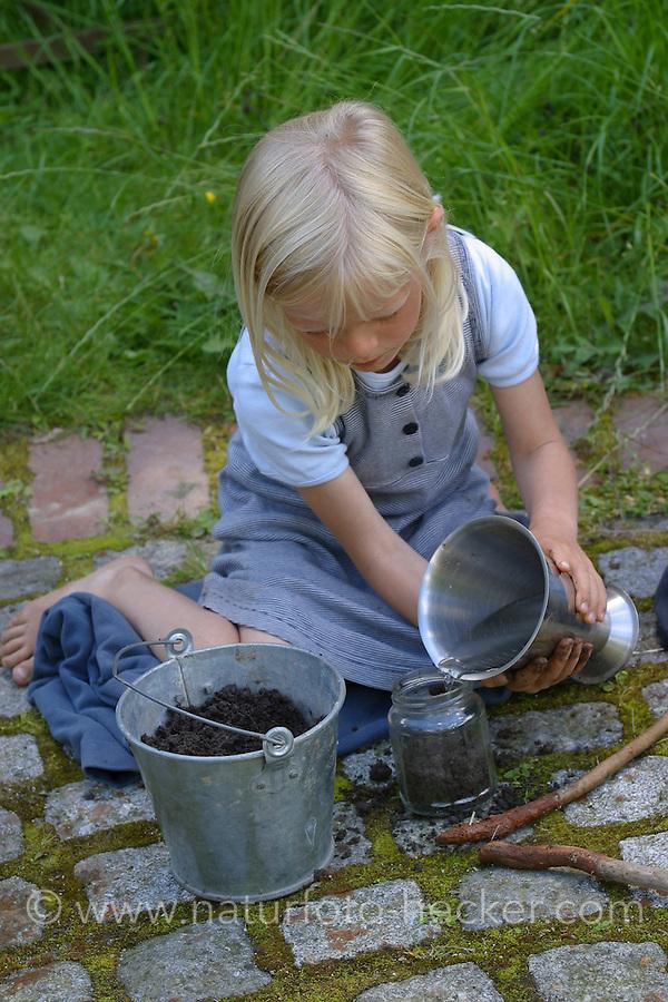 Kinder malen mit selbstangemischten Erdfarben, Farbe aus verschiedenfarbiger Erde, Farbe wird in einem Glas mit Wasser, Kleister und Erde angemischt