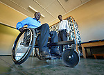 Lucky Chirambaterere (right), a technician at the National Rehabilitation Centre in Ruwa, Zimbabwe, watches as Sunny Nyamandwe tries out a wheelchair in the Centre, which assembles and fits wheelchairs provided by the Jairos Jiri Association with support from CBM-US.