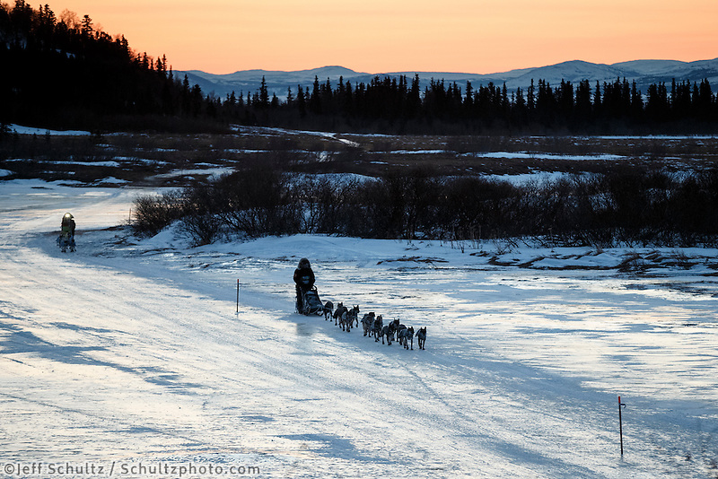 Pete Kaiser leads Wade Marrs on the Unalakleet River at sunrise on the way in to Unalakleet on Sunday, March 9, during the Iditarod Sled Dog Race 2014.<br /> <br /> PHOTO (c) BY JEFF SCHULTZ/IditarodPhotos.com -- REPRODUCTION PROHIBITED WITHOUT PERMISSION