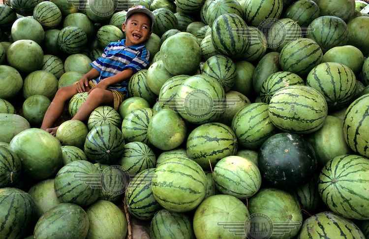 A young child sitting amongst a heap of watermelons at the Central Market.