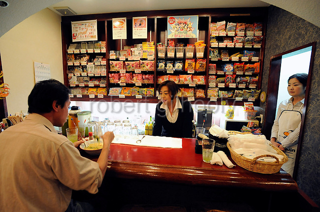 Kazuo Tateishi, a 44-year-old garbage recycler, enjoys a bowl of instant noodles as at the counter of Instant Noodle Sakura in Tokyo, Japan on 06 November 2008. The pub-cum-eatery boasts a menu of fine wines, cocktails, around 80 types of instant noodles and 10,000 karaoke tunes..