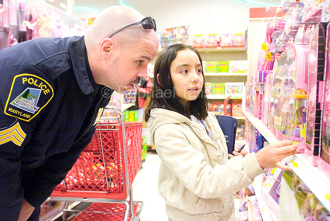 The Gazette SGT. Gordon Pracht of the Greenbelt Police helps Janeth Martinez, 9 of Greenbelt shop for Christmas gifts for her family at the Target at Beltway Plaza Mall on Saturday morning. The Shop with a Cop program, put on by the Greenbelt Fraternal Order of Police pairs a police officer with a child in need and gives them $100 to shop.