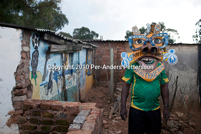 JOHANNESBURG, SOUTH AFRICA - MAY 10: Alfred Baloyi, an artist, and the founder of the Makarapa Helmet stands outside his old studio in a squatter camp with one of his early Makarapas in Primrose, Johannesburg, South Africa. Mr. Baloyi, and a diehard Kaizer Chiefs soccer fan, started to make these hats in 1979. Initially he asked a friend who worked at a construction site for a helmet, as he wanted to protect himself from missiles at games. He later started to paint it, and later started to make this different figures hand cut out from the helmet. During the years he has made many different artistic hats that are on display in his studio in a shack in Primrose, Johannesburg. He later gave up his job as a washer of busses. From his small workshop in a squatter camp in Primrose south east of Johannesburg he recently made partner with an investor and have a brand new factory with about fifty people employed to make the hats. (Photo by Per-Anders Pettersson/Getty Images)