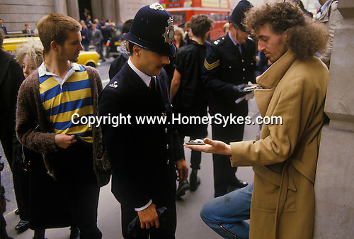 Reclaim the City demonstration 1980s  Demonstration against capitalism City of London England. 1984. Police search man. outside of the Bank of England.