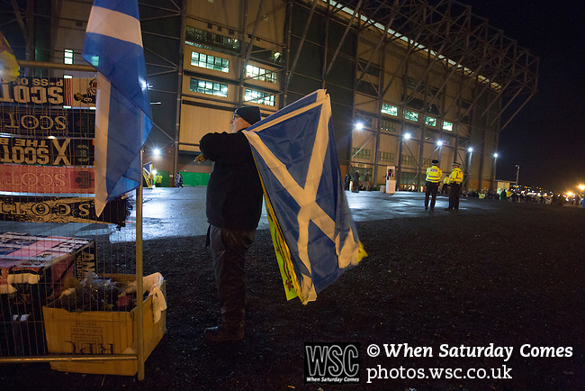 Scotland 1 Republic of Ireland 0, 14/11/2014. Celtic Park, European Championship qualifying. A souvenir seller with saltire flags for sale outside the stadium before the European Championship qualifying match between Scotland and the Republic of Ireland at Celtic Park, Glasgow. Scotland won the match by one goal to nil, scored by Shaun Maloney 16 minutes from time. The match was watched by 55,000 at Celtic Park, the venue chosen to host the match due to Hampden Park's unavailability following the 2014 Commonwealth Games. Photo by Colin McPherson.