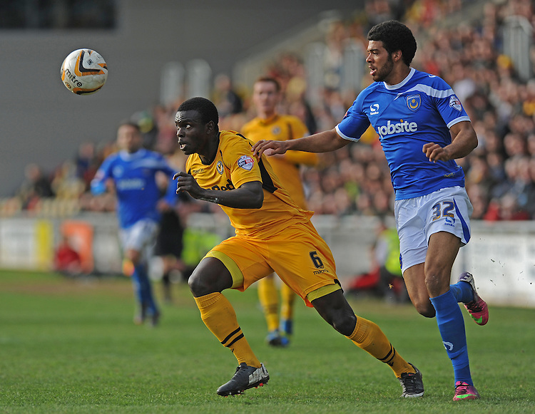 Newport County's Ismail Yakubu vies for possession with Portsmouth's Jake Jervis<br /> <br /> Photo by Ashley Crowden/CameraSport<br /> <br /> Football - The Football League Sky Bet League Two - Newport County AFC v Portsmouth - Saturday 29th March 2014 - Rodney Parade - Newport<br /> <br /> &copy; CameraSport - 43 Linden Ave. Countesthorpe. Leicester. England. LE8 5PG - Tel: +44 (0) 116 277 4147 - admin@camerasport.com - www.camerasport.com