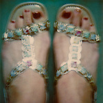 Woman's feet with painted toenails in fancy gold sandals