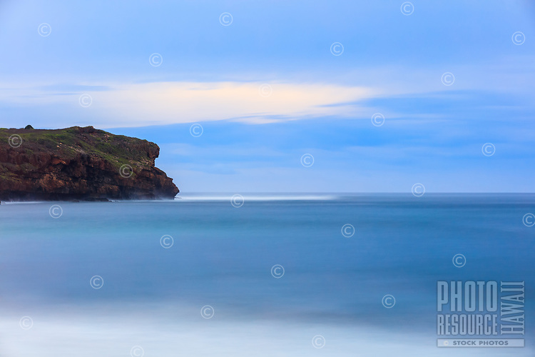 A long-exposure image taken during a hike reveals the calming blues of an overcast sky and glassy seas against the rugged coastline of Kaua'i's south shore.