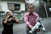 Kouzaburo Sakurai holds an AIBO while his wife Michiko Sakurai photographs it near their home in Tokyo.  In 1999, Sony released a series of robotic pets called AIBO or Artificial Intelligence Robot. In 2006, they discontinued the AIBO line and then in 2014, discontinued all reparair services on the AIBO. A small community of AIBO owners still exists and a new repair service has emerged to help keep the AIBOs running.