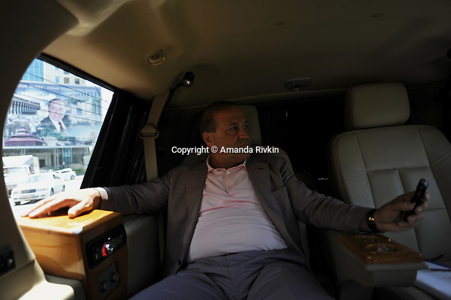 Ibrahim Ibrahimov, an Azerbaijani oligarch and billionaire, looks at his cell phone while driving passed one of several ubiquitous portraits of former Azerbaijani President Heydar Aliyev, also father of the current president, in Statistika in Baku, Azerbaijan on July 18, 2012.  The brainchild of Ibrahimov, the artificial Khazar Islands project just southwest of the Azerbaijani capital Baku is being built at a projected cost of $100 billion with an anticipated 800,000 housing units.