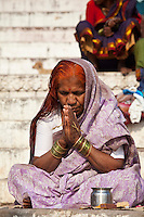 Indian Hindu pilgrims  praying by The Ganges River at Dashashwamedh Ghat in Holy City of Varanasi, Benares, India