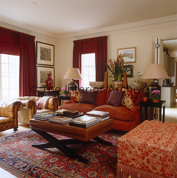 With walls bathed in a custom sand color, the red cotton curtains and red chenille sofa warm up the natural palette