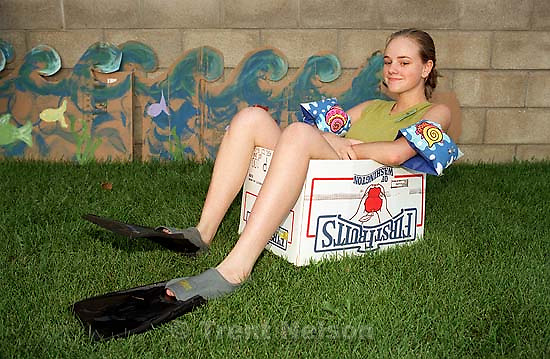 Camille Robinson sitting in a box with flippers on at a family get-together.<br />