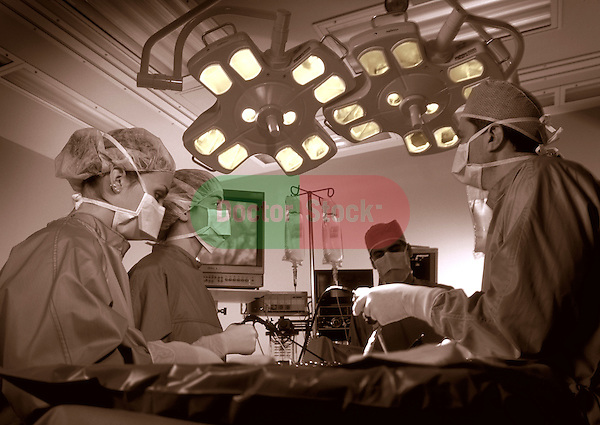 surgical team gathered around operating table, brown duotone