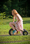 Young redheaded woman riding tricycle