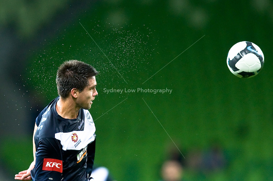 MELBOURNE, AUSTRALIA - May 14, 2010: Beads of perspiration surround Rodrigo Vargas from Melbourne Victory after he heads the ball during the Kevin Muscat Testimonial match between the Melbourne Victory and Come Play XI at AAMI Park on May 14, 2010 in Melbourne, Australia. Photo Sydney Low www.syd-low.com